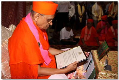 Acharya Swamishree reads the plaque that was presented to him