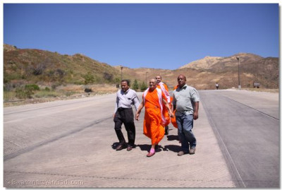 Acharya Swamishree, sants, and disciples walk to the lake area
