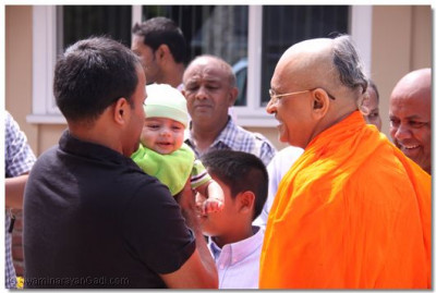 Acharya Swamishree gives His divine darshan to a very young discple as He departs