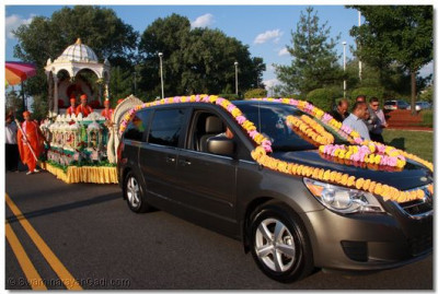 A decorated vehicle pulls His Divine Holiness Acharya Swamishree and Sants seated on the magnificent chariot