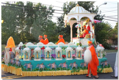His Divine Holiness Acharya Swamishree and Sants seated on the magnifcent intricately decorated welcoming chariot as it proceeds around the temple grounds
