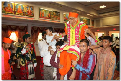 Disciples carry His Divine Holiness Acharya Swamishree through the main temple hall at Shree Swaminarayan Temple New Jersey