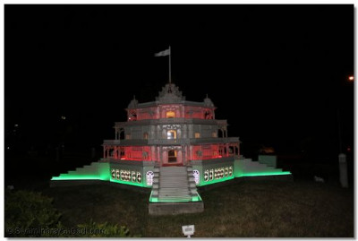 The view of the beautiful Smruti mandir model lit with green, orange and white lighting, located within the grounds of Shree Swaminarayan Temple New Jersey