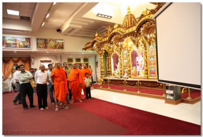 Acharya Swamishree observes the new self-installed automated projector screen in the temple