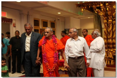 Disciples escort Acharya Swamishree from the temple