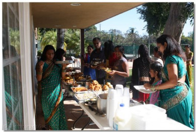Disciples enjoy prasad from the ankoot