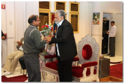 The temple vice-president welcomes  Mr. Parshottam Rupala with flowers