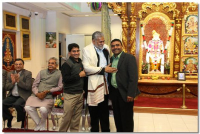 The temple Treasurer presents a shawl to Mr. Parshottam Rupala