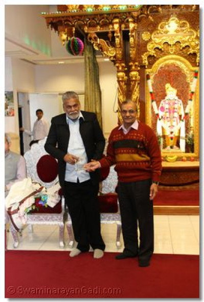 A temple disciple presents a momento to Mr. Parshottam Rupala