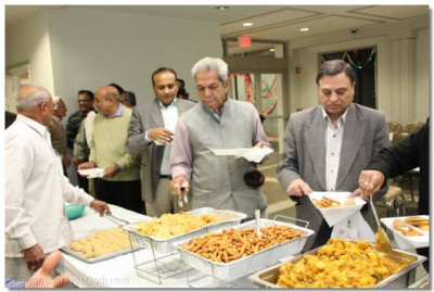 Guests of honor and disciples enjoy a full dinner prasad