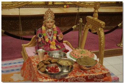 Lord Swaminarayan, seated on a swing, is presented with various delicacies to celebrate his birthday