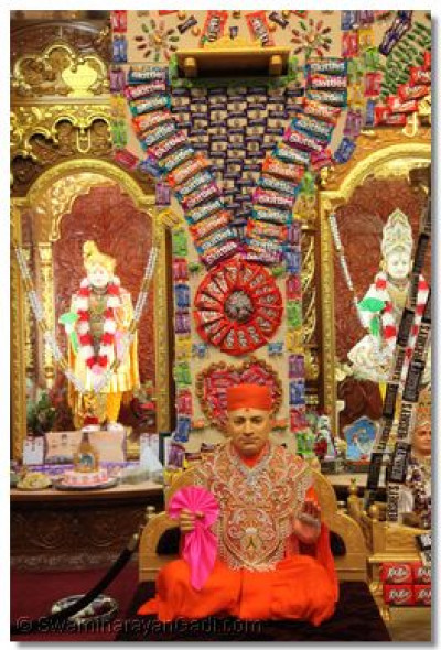 Divine darshan of Jeevanpran Shree Muktajeevan Swamibapa seated in front of the candy hindolo