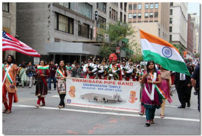 Temple volunteers hold a banner and wave American and Indian flags, proudly representing the temple and displaying patriotic pride