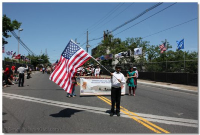A disciple proudly waves the American flag in the front of the parade