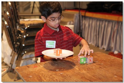 A young disciple is challenged to stack three blocks on a plate using only one hand