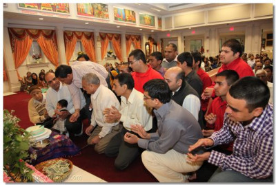 Disciples  participate inthe cake-cutting ceremony to celebrate Lord Shree Swaminarayan's birthday