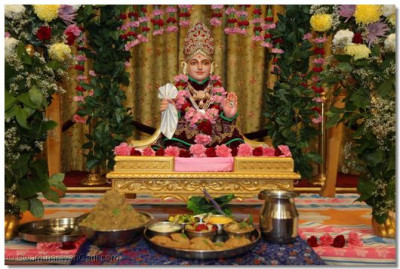 The divine darshan of Lord Shree Swaminarayan sitting on a swing decorated with fresh flowers