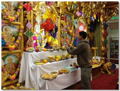 A disciple offers Lord Shree Swaminarayan cake