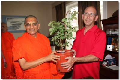 A local community member presents Acharya Swamishree with a plant