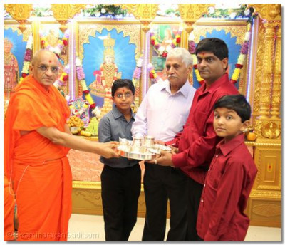 Disciples present Acharya Swamishree with a new set of dishes and eating utensils for Lord Swaminarayanbapa Swamibapa's thaal