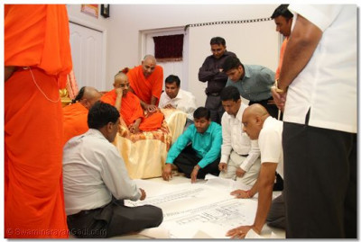 Acharya Swamishree, sants, and disciples look at the blueprints for the new sikhar-bandh temple to be built