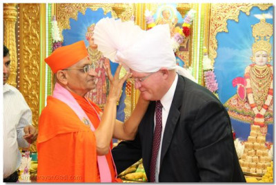 Acharya Swamishree applies chandlo to an honored guest