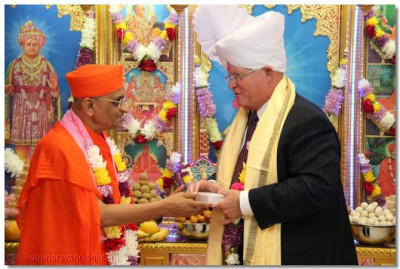 Acharya Swamishree offers prasad to the honored guest