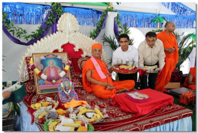 Acharya Swamishree blesses disciples who have brought offerings for the Lord