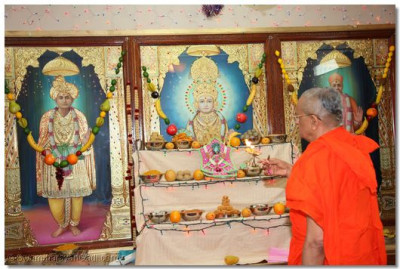 His Divine Holiness Acharaya Swamishree performs aarti to Supreme Lord Shree Swaminarayan