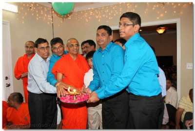 Disciples perform the aarti of Lord Shree Swaminarayan with Acharya Swamishree