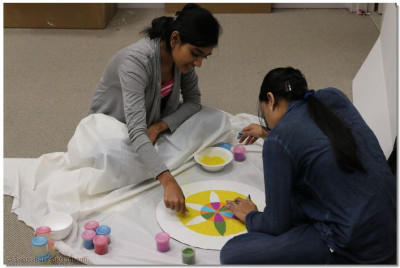 Disciples create colorful crafts (rangoli) to decorate the temple hall