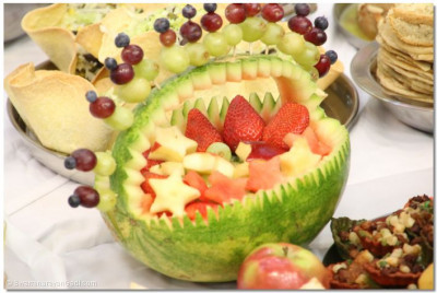 A watermelon carriage is decorated with assorted fruits
