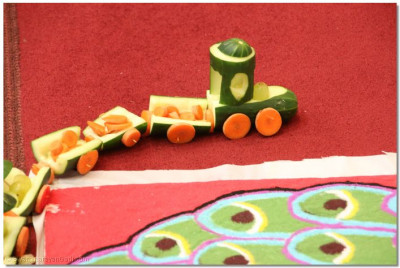 A train made of cucumbers, carrots, and grapes circles the perimeter of the rangoli display