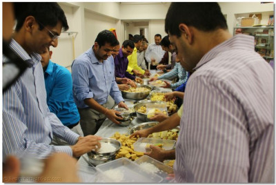 Disciples carefully package the prasad for distribution
