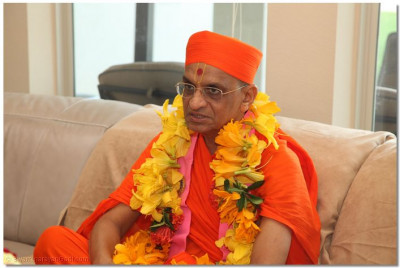 Divine darshan of Acharya Swamishree wearing a garland made from local Texas flowers