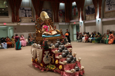 Divine darshan of Lord Shree Swaminarayan seated on a grand throne amidst a steel utensil display