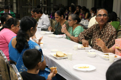 Disciples enjoy mahaprasad at the end of the evening