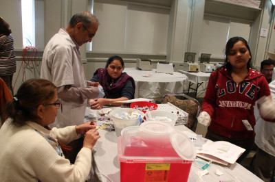 Temple volunteers assist the doctors at the blood test station