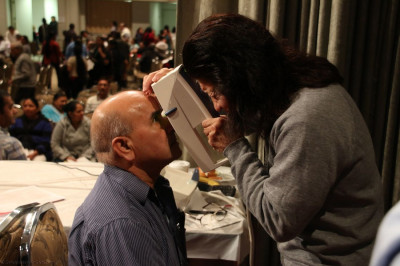 A doctor performs an eye-screening