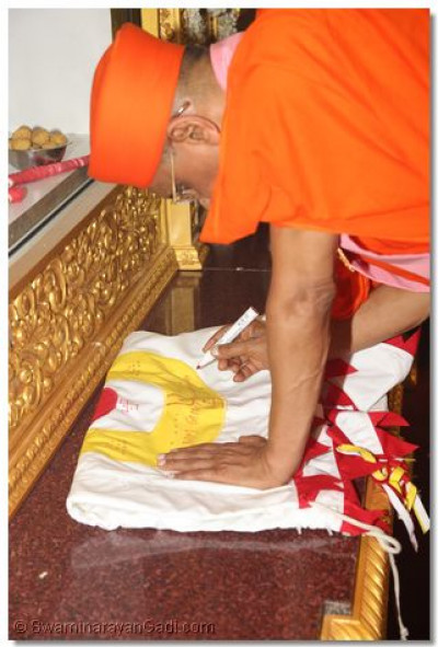 Acharya Swamishree prepares the flag to be hung on the temple flagpole