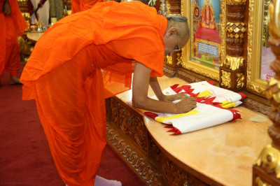 Acharya Swamishree consecrates the new flags that will fly over the temple domes until the next patotsav