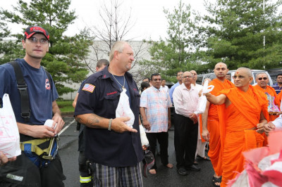 Acharya Swamishree offers prasad to the Secaucus Fire Department volunteers