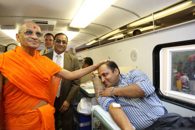 Acharya Swamishree blesses a disciple donating blood, a very selfless act of devotion