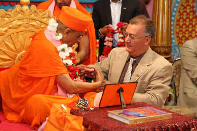 Acharya Swamishree ties a raakhi on the right wrist of Mayor Gonnelli