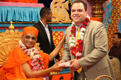 Acharya Swamishree presents Hudson County Sheriff Frank Schillari with a box of consecrated sweets