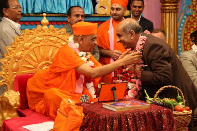 Acharya Swamishree garlands Ramanbhai Patel, who is a major asset to the temple�s Public Relations department