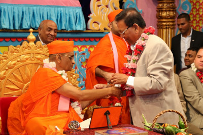 Acharya Swamishree ties a raakhi on the right wrist of Jitendrabhai Fadia, New Jersey Health Camp organizer