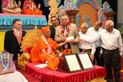 Acharya Swamishree and disciples present $1000 donations for each the Secaucus Fire Department and the Emergency Relief Fund to Mayor Gonnelli