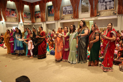 Disciples perform aarti at the conclusion of the scripture recitals