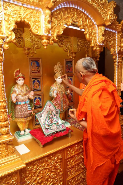 Acharya Swamishree applies chandlo to Lord Shree Swaminarayan